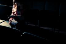 woman sitting in a dark empty church reading a Bible