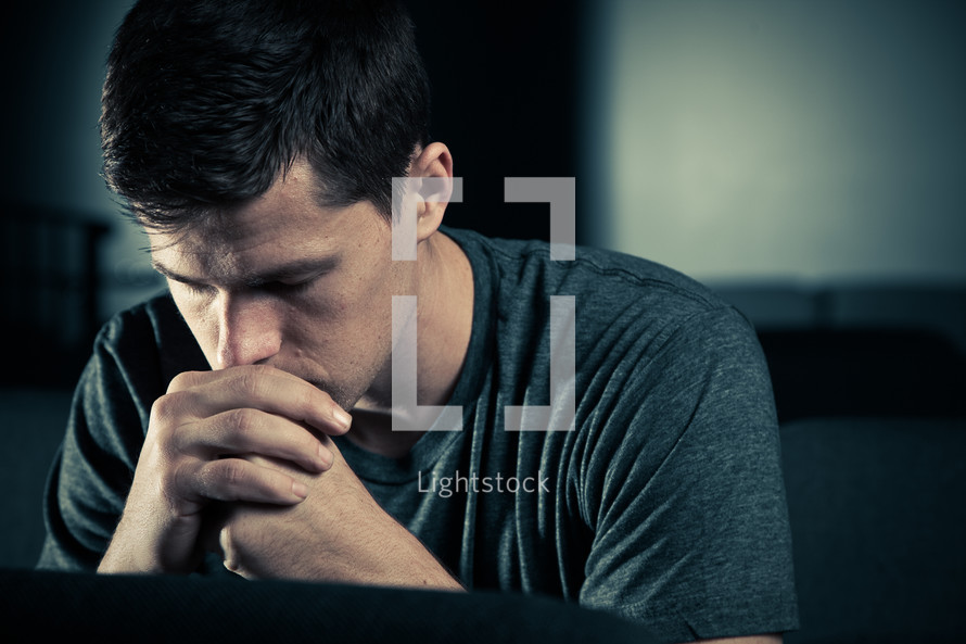 man sitting with his head bowed in prayer