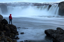 a person watching a waterfall in Iceland