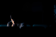 man sitting in a dark empty church with his head bowed in prayer