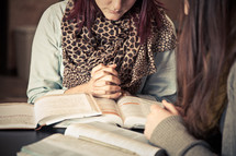 young women in prayer over Bibles at a Bible study