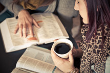 young woman holding a cup of coffee as she read and discusses scripture at a Bible study