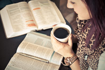 woman holding a cup of coffee and reading a Bible at a Bible study