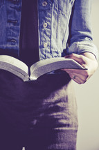 close-up of the pages of a Bible as a woman reads