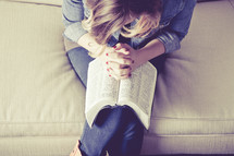 woman with her hands held in prayer over the pages of a Bible