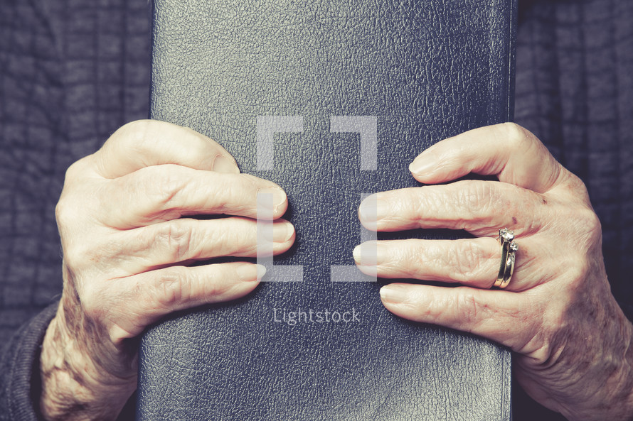 hands of an elderly woman holding a Bible