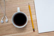 earbuds, coffee mug, pencil, paper