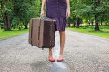 woman standing on a rural road holding luggage