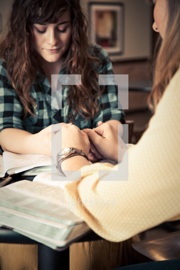 Two women holding hands and praying during a Bible study.