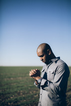 man in prayer in a field