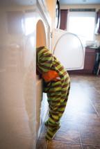 toddler boy in pjs looking in a dryer