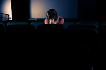 woman sitting in a dark empty church with her head bowed and her hands covering her face