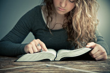 Girl studying Bible open on wooden table.