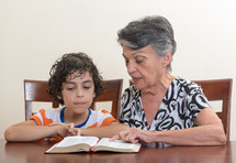 a grandmother reading the Bible to her grandson