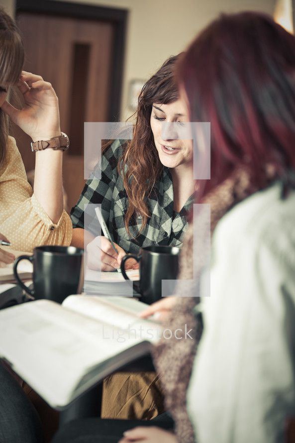 Three women drinking coffee during a Bible study.