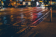night lights reflect on a rainy city street with tram tracks