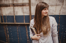 a young woman holding a Bible
