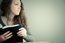Teenage girl in thought holding open Bible.