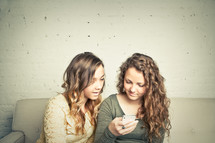 two teen girls looking at their cellphone