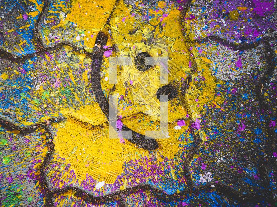 a yellow paint splash on a sidewalk pavement turned into a smiley face emoji