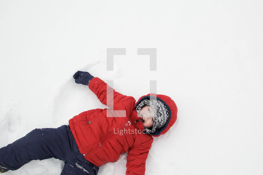 child making snow angels in the snow