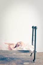 newborn baby lying on a doll bed