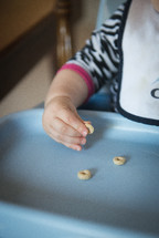 an infant in a highchair eating Cheerios
