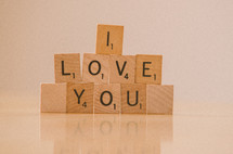 """I love you"" arranged in stacked scrabble tiles on reflective table top."