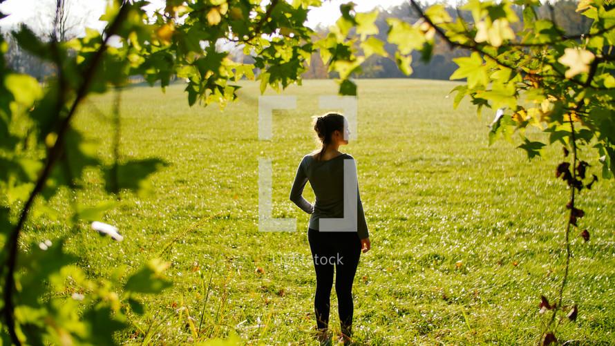 woman standing in a field of cut green grass