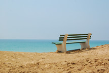 bench on a beach overlooking the ocean