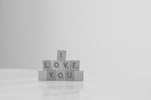 """I love you"" spelled in stacked scrabble tiles in black & white."