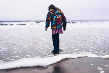 a child in a coat and boots walking on a shore