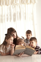 mother reading Bible stories to her children