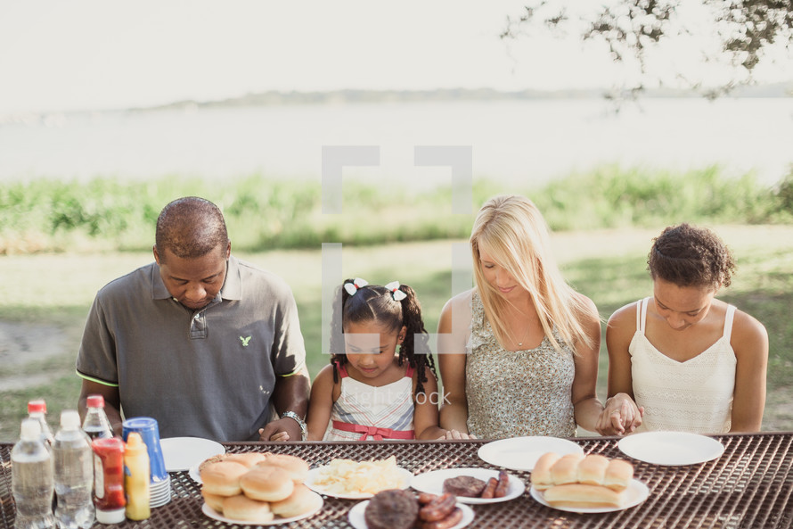 family holding hands in prayer at a picnic table
