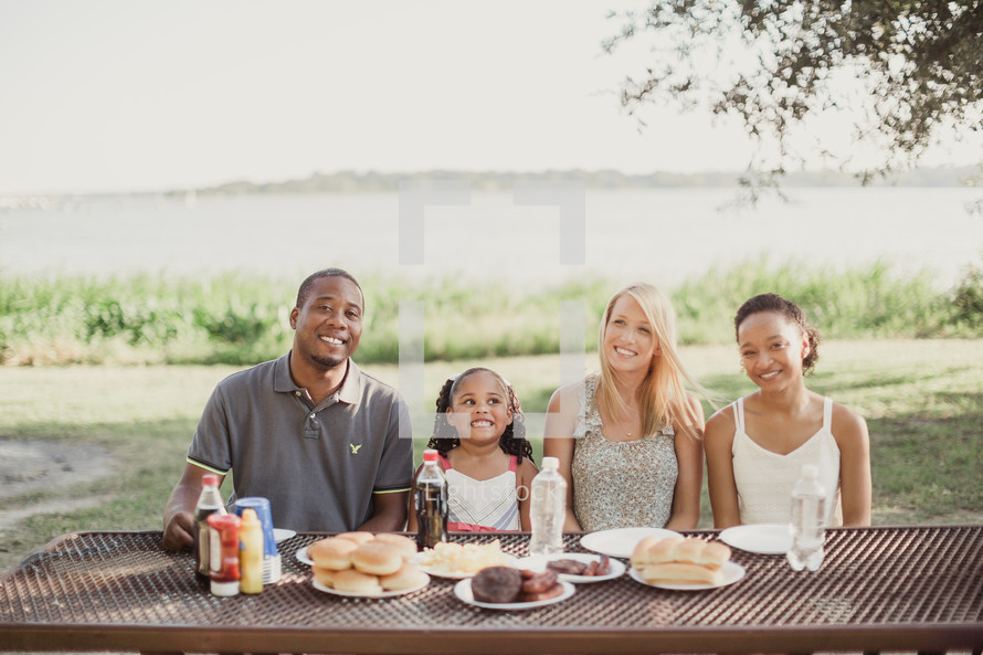 a family sitting at a picnic table