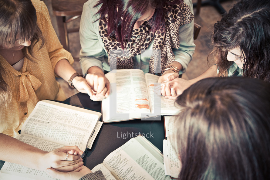young women holding hands in prayer over Bibles at a Bible study