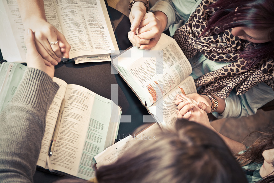 women holding hands in prayer over Bibles
