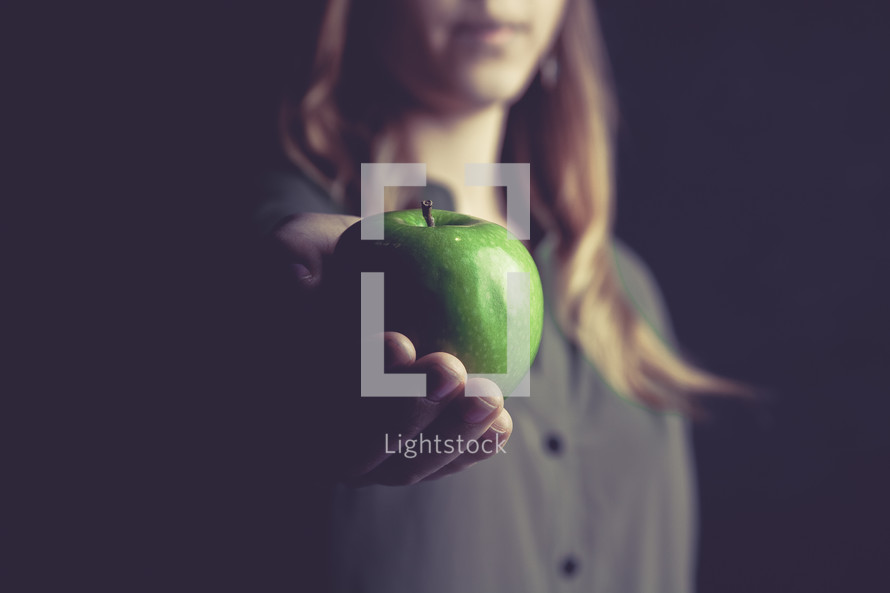 woman holding out a green apple