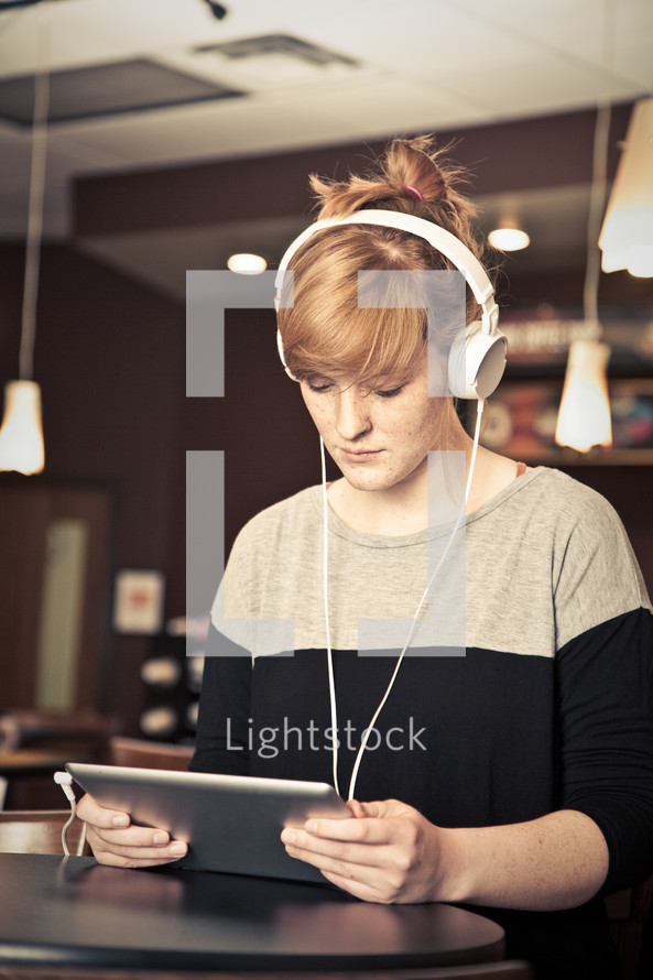 young woman looking at an iPad with headphones on