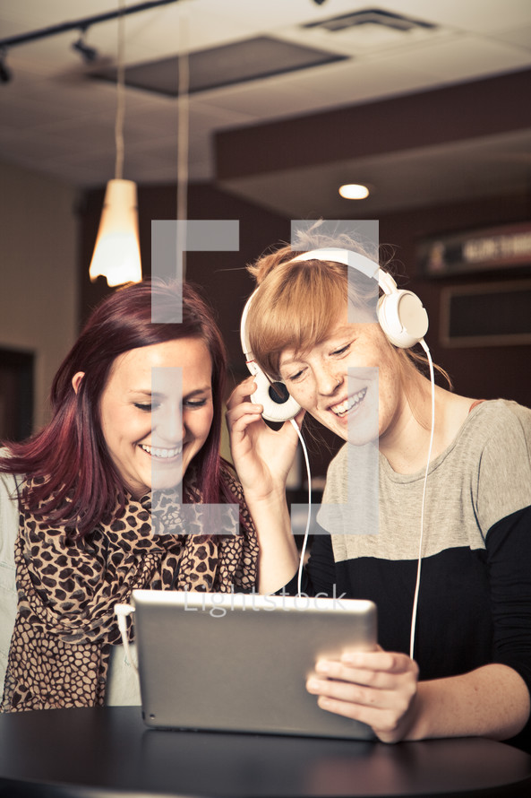 Two girls listening to something on an iPad.