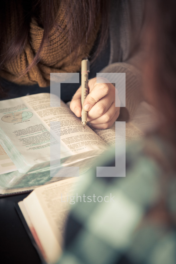 young woman underlining scripture in a Bible