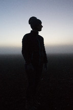 silhouette of a woman standing outdoors in a beanie