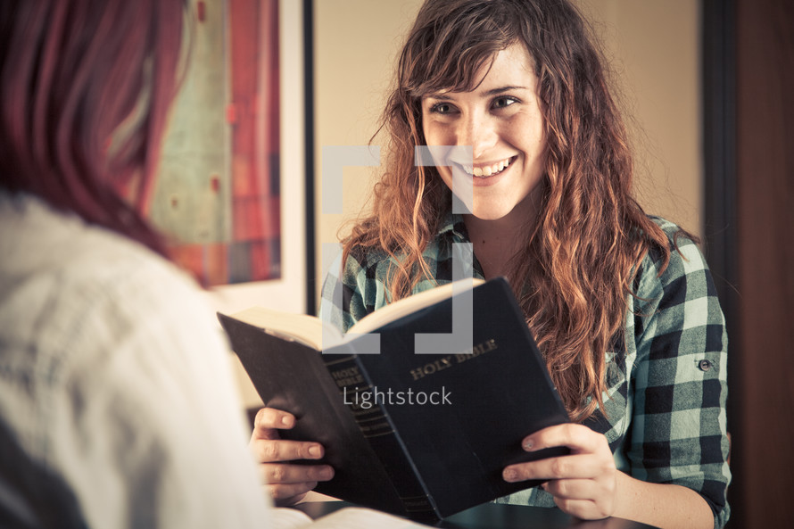 young women reading and discussing a Bible and smiling