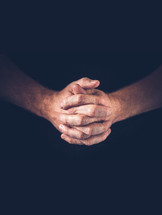 A vertical shoot of hands closed in prayer