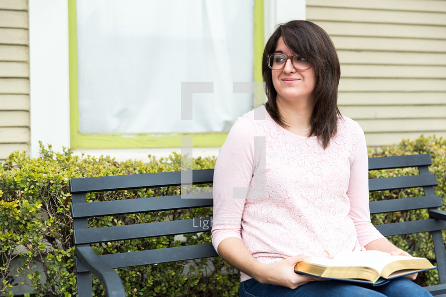 a brunette woman sitting on a bench with a book
