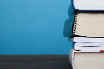 A stack of books on a wooden surface against a blue background.