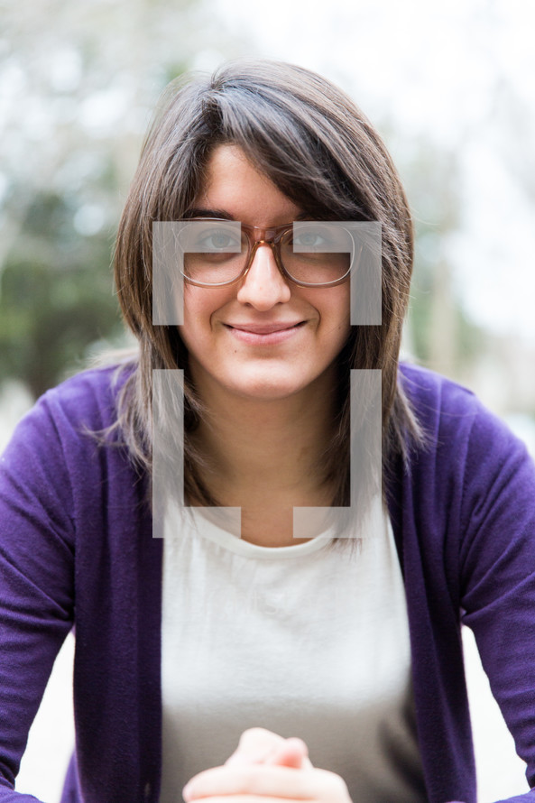 a brunette woman with reading glasses and praying hands