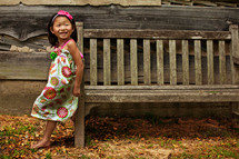 girl child in a dress leaning on a wood bench