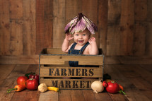infant on a farmers market crate
