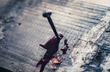 A bloody nail is hammered into an old wooden cross beam